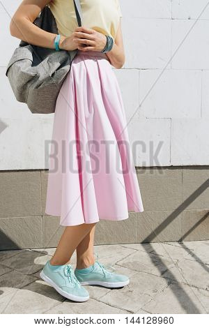 Girl In Pink Skirt, Yellow Shirt And With A Backpack Standing Against A White Wall