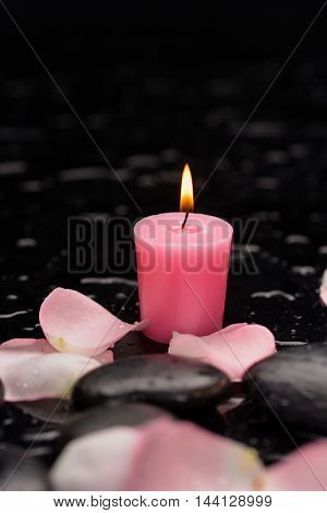 Still life with rose petals with candle and therapy stones