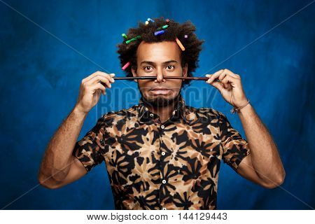 Young handsome african man with markers in hair fooling over blue background. Copy space.