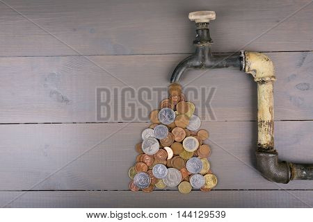 faucet with coins - money is not a problem