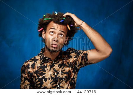 Young handsome african man with markers in hair thinking over blue background. Copy space.