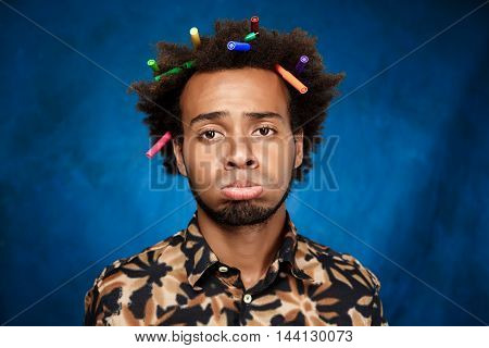 Sad young african man with markers in hair over blue background. Copy space.