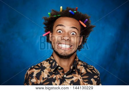 Young handsome african man with markers in hair smiling over blue background. Copy space.
