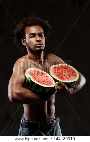 Young sportive african handsome man holding watermelon, posing over black background. Copy space.
