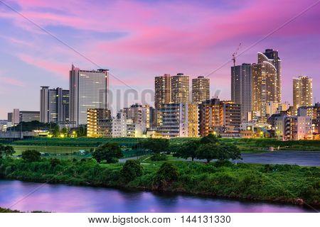 Kawasaki, Japan skyline on the Tamagawa River at twilight.