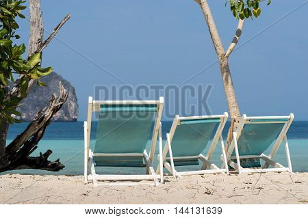 three beach chairs on sand and sea view for background