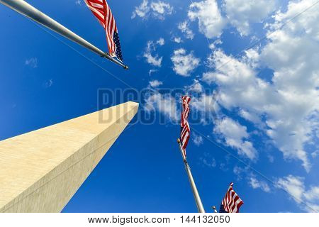 Washington Monument and US flags with cloudy sky background