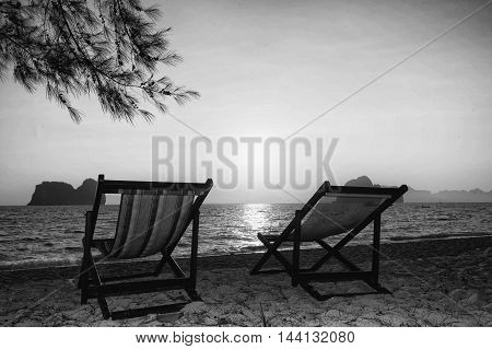 double beach chair on sand in b&w filter black and white photo