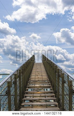 straight metallic stairway leading to the cloudy sky by daytime