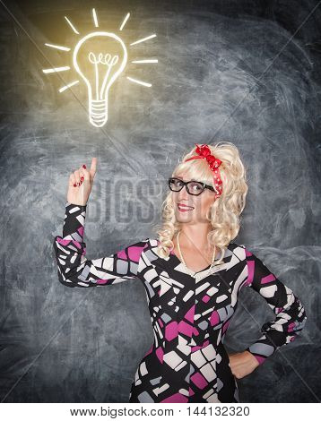 Retro woman showing on drawing lamp by finger on the blackboard background