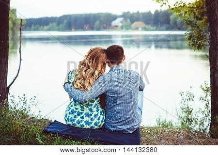 Young couple embracing sitting back looking at the lake.