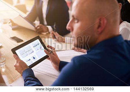 tablet being used in a business meeting with graphs on the display by a caucasian businessman wearing a blue shirt to provide live financial analysis.