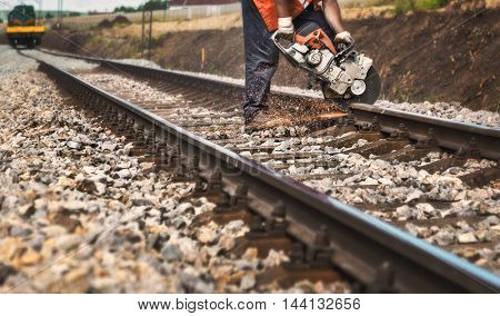 Reconstruction of the railway -Worker on the railway cuts rail with a machine