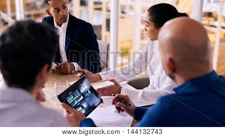 Group of four business people talking to each other during a business meeting with a caucasian man holding an electronic tablet in his hands with graphs and charts on the display.