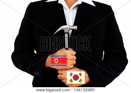 business man hold hammer with north and south korea flag on white background