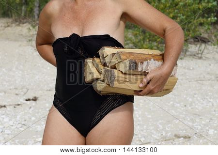 tourism and a healthy lifestyle, outdoors girl in swimsuit . stands and holds the firewood of birch
