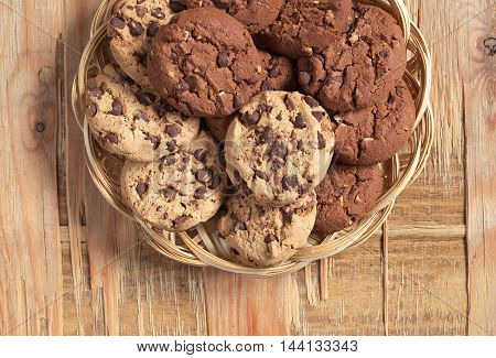 Cookies with chocolate and nuts in wicker plate on old wooden background top view