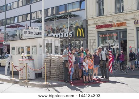 BERLIN GERMANY - AUGUST 25 2016: Tourists Posing At Historic US Army Checkpoint Charlie In Berlin Germany