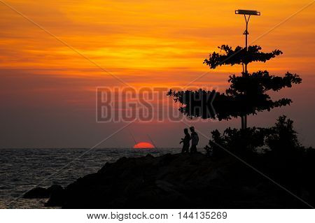 Silhouette of group of fisherman enjoying beatiful sunset and fishing over the stone embankment at Labuan Pearl Of Borneo,Malaysia.