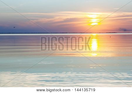 Lake tranquil pink sunset landscape above water waves