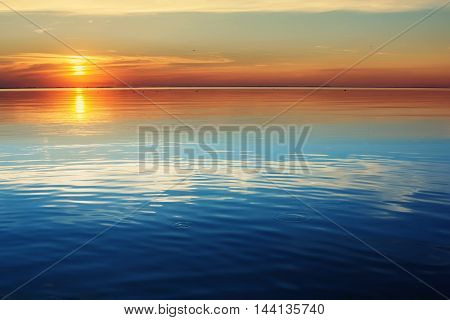 Lake tranquil sunset landscape above water waves