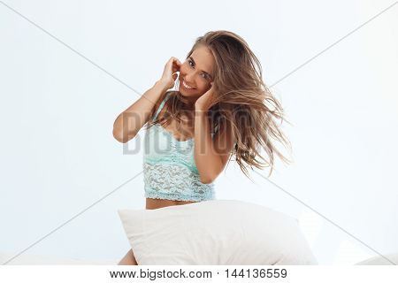 Young beautiful girl smiling, sitting on bed early in morning.