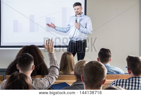During lecture one of the student is raising a hand to ask a question