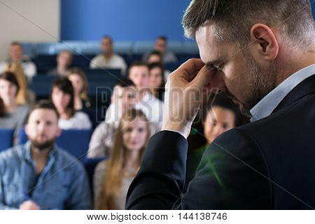 Lecturer stands in front of a full house and pinches the bridge of his nose