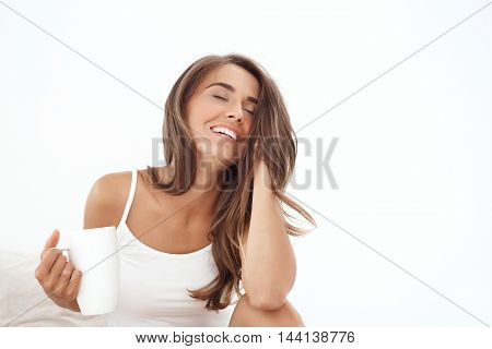 Young beautiful girl smiling, sitting on bed, drinking tea early in morning.