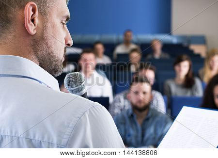 Speaker during presentation is looking at his notes