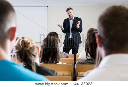 Smiled lecturer is explaining something to his students in a classroom