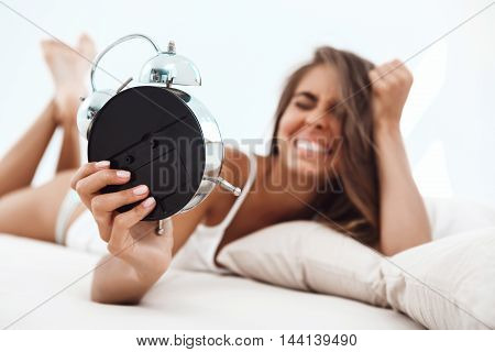 Displeased young beautiful girl lying on bed, looking at alarm-clock early in morning.  early in morning.