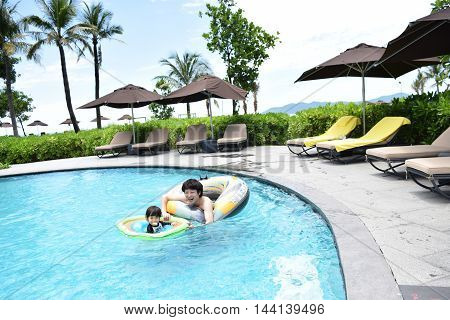 Japanese father and son playing at summer pool