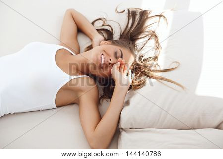 Young beautiful girl smiling, lying on bed early in morning.