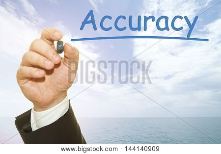 Businessman hand writing Accuracy word on a transparent wipe board.