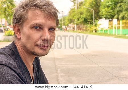 Unshaven man sitting outdoor and doing selfie photo