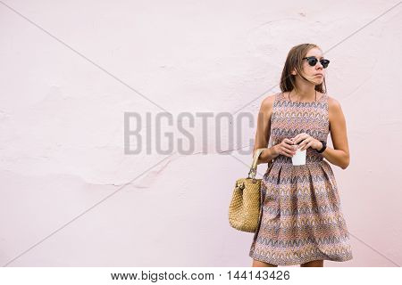 portrait of young brunette woman in dress and sunglasses against of light pink background with coffee to go.Copy space