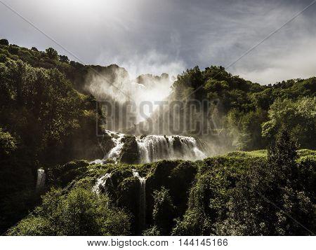 big waterfalls among the trees sunny day