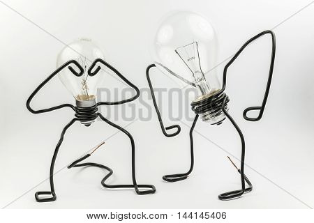 Two emotional fantasy figures of transparant light bulbs and black electrical wires