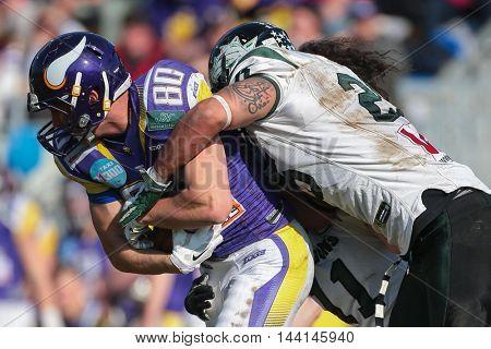 VIENNA, AUSTRIA - APRIL 19, 2015: LB Ramon Azim (#25 Dragons) tackles  WR Nikolaus Knehs (#80 Vikings) in a game of the Austrian Football League.
