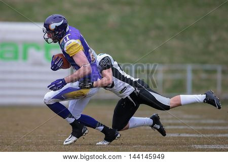 VIENNA, AUSTRIA - MARCH 22, 2015: DB Patrick Pilger (#20 Raiders) tackles WR Manuel Thaller (#11 Vikings) in a game of the Austrian Football League.