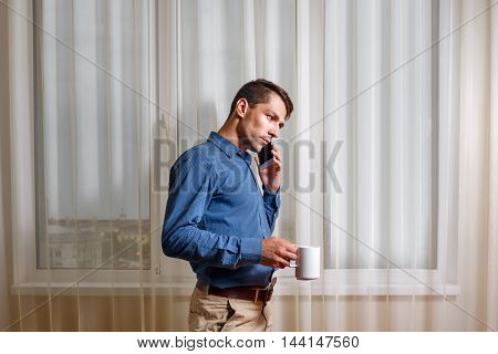 Businessman talking on the phone and drinking coffee in the early morning. Freelancer at work. The difficult negotiations.