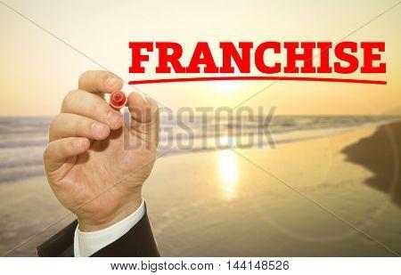 Businessman hand writing FRANCHISE word on sunset.