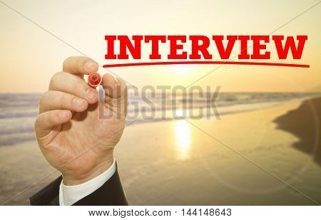 Hand writing INTERVIEW word on sunset background.