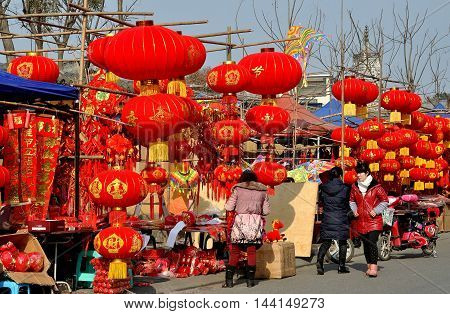 Pengzhou China - January 21 2014: Bright red lanterns and other Chinese New Year decorations sold by vendors line the street at the Long Xing outdoor marketplace