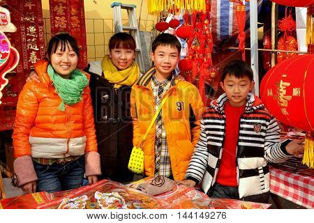 Pengzhou China - January 21 2014: Family members selling Year of the Horse decorations and toys for the Chinese New Year holiday at the Long Xing outdoor marketplace