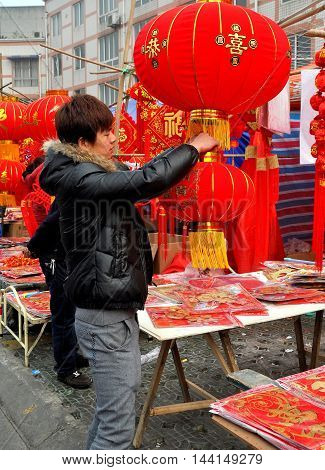 Pengzhou China - January 29 2014: Man examines a big red lantern decoration for the Chinese Lunar New Year holiday