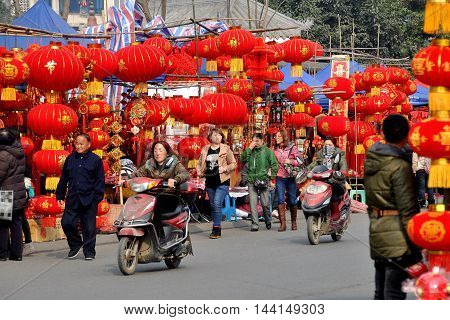 Pengzhou China - January 23 2014: People shopping for Chinese Lunar New Year holiday decorations at the Long Xing outdoor marketplace