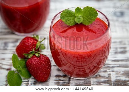 strawberry smoothie on a light wooden background