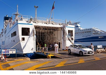 Naples Italy - August 10 2016: At the pier in the port of Naples a man in the car makes reversing to board the ferry to the island of Ischia in the maneuver helped by the crew.